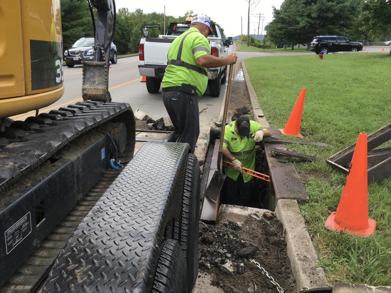 Photo of public works employees repairing drain