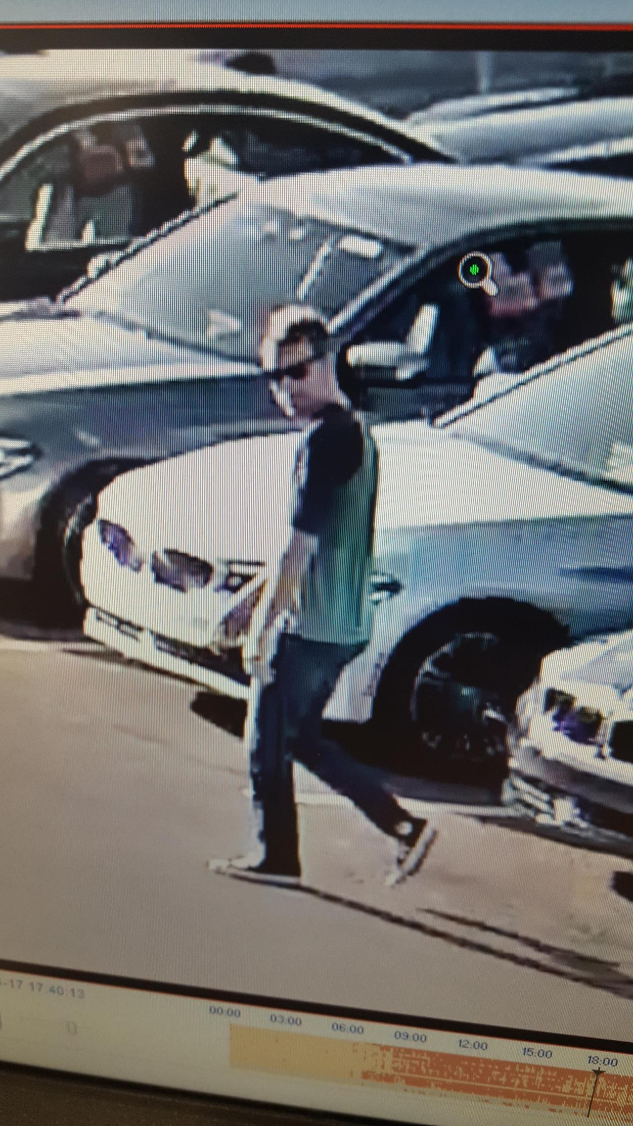 suspect walking by cars wearing sunglasses