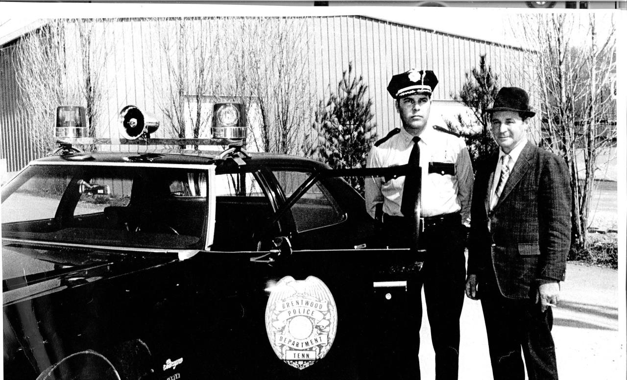 two police officers standing near old car