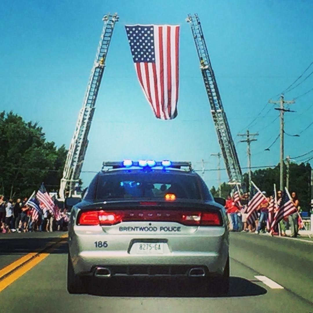 Photo of a Brentwood Patrol Car Under a Large American Flag