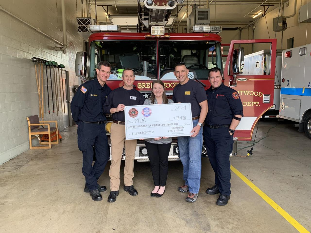 photo of men and women standing infront of a fire truck with large check