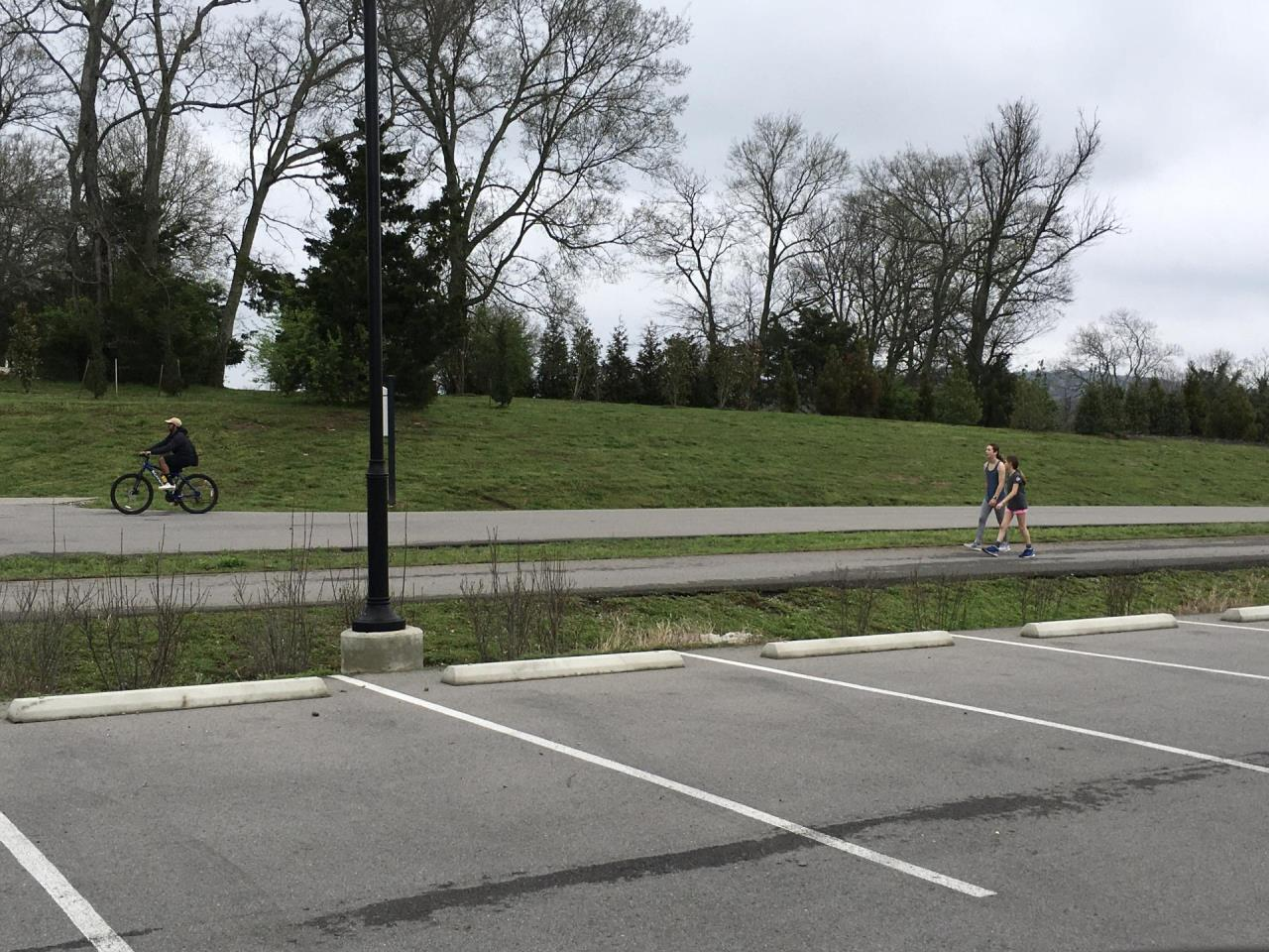 image of a cyclist and people walking six feet apart at a park