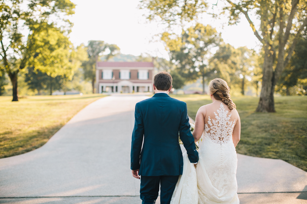 Bride and Groom holding hands walking up a driveway with a house in the distance